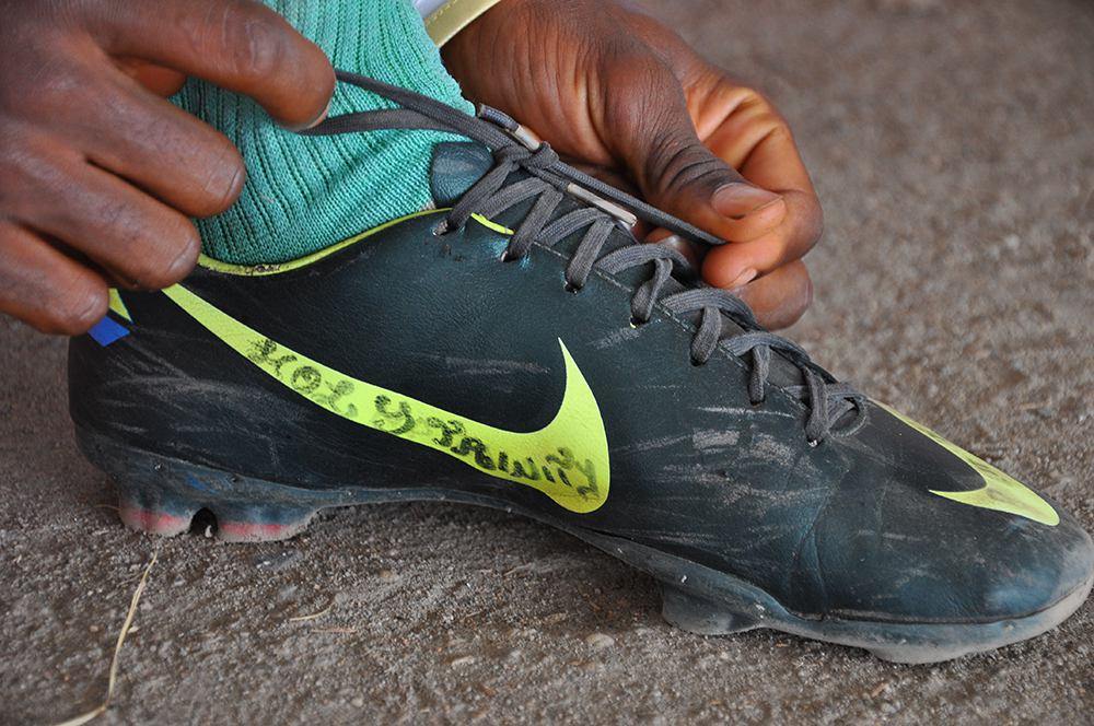 "Uros Kovac - football, boot, Buea, 2014. An inscription on a footballer's boot reads ""Holy Trinity"". Charismatic Christianity allows the young athletes the grapple with uncertainty. Buea, Cameroon, December 2014. Photo by Uroš Kovač."
