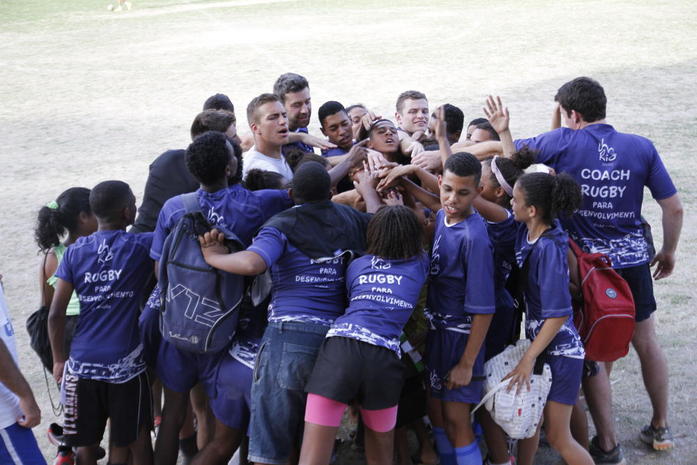 Volunteers and participants form a huddle to mark the end of a training session, Morro do Castro, 2015