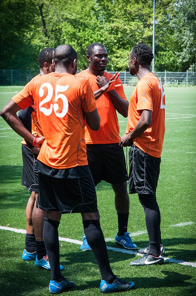 Ifechi and Ifeanyi (both on the right) discuss a plan for the second half of the game (their side trailed 0-3 with the team composed of active players), while two of their teammates stand close and listen. Ifechi and Ifeanyi, who have been in Poland for almost a decade, are prominent figures in the park community, and both served in the past as presidents of PolBlack. Warsaw, Summer 2016. (Photo Paweł Banaś)