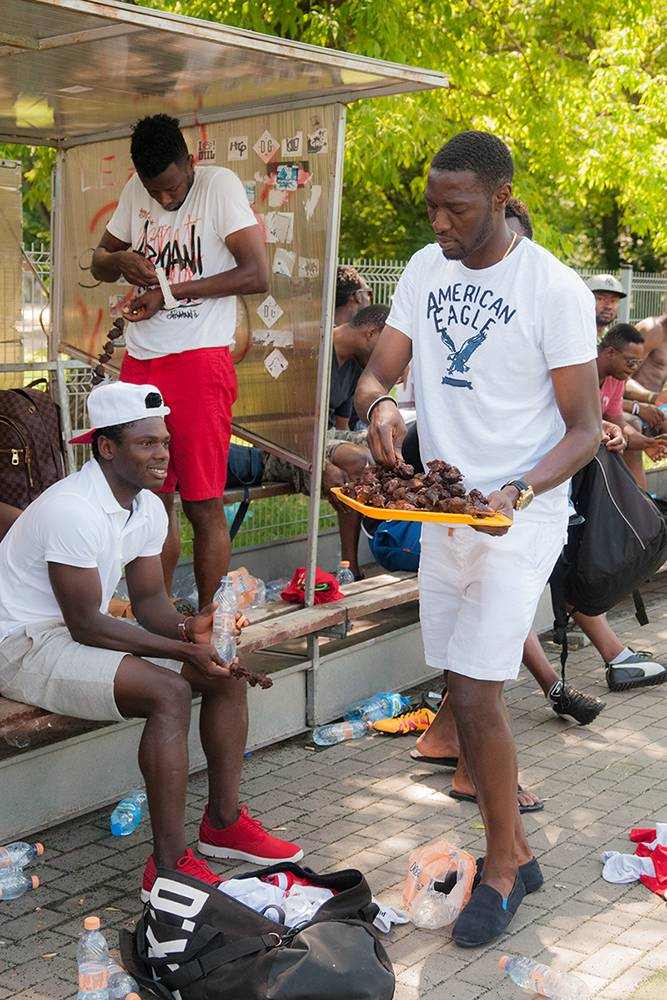 Olabode, who recently got married, hands out barbecued chicken to his friends in the park. West African football migrants often hold informal parties in the park. Weddings, the birth of children, and other important occasions are celebrated with food, drinks, music and dances. Warsaw, Summer 2016. (Photo Paweł Banaś)
