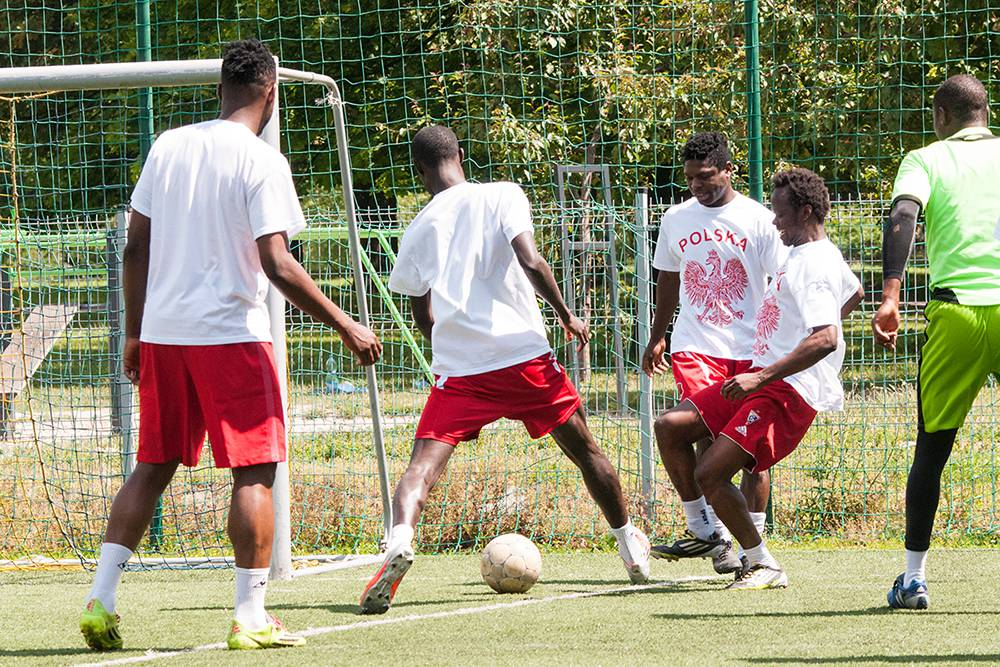 West African football players who currently play in Poland warm up before a friendly game with former players doing rondo, a popular practice in which a group of players standing in a circle pass the ball to one another while two footballers in the middle of the circle try to intercept the ball. Warsaw, Summer 2016. (Photo Paweł Banaś)